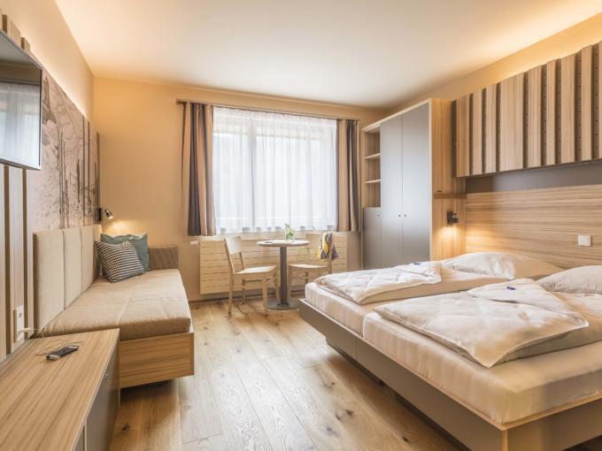 Doppelbett im Doppelzimmer plus im JUFA Hotel Malbun Alpin-Resort mit Sofa. Der Ort für erholsamen Familienurlaub und einen unvergesslichen Winter- und Wanderurlaub.