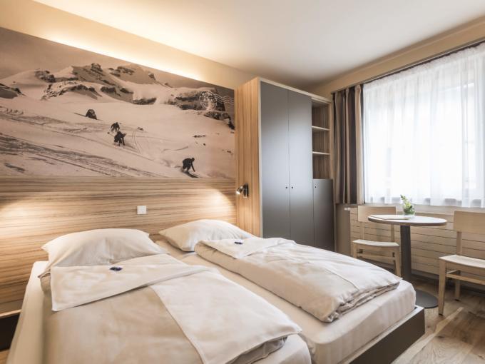 Doppelbett im Doppelzimmer im JUFA Hotel Malbun Alpin-Resort mit Fensterund einem Bild über dem Bett. Der Ort für erholsamen Familienurlaub und einen unvergesslichen Winter- und Wanderurlaub.
