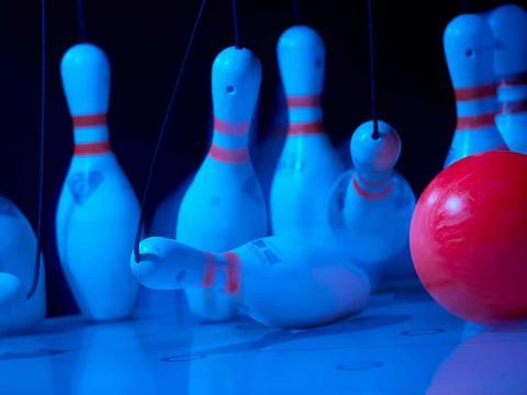 Eine rote Bowlingkugel trifft auf Bowling Pins in der Bowlinganlage in der Inseltown in Pöllau in der Nähe von JUFA Hotels. Der Ort für erholsamen Familienurlaub und einen unvergesslichen Winter- und Wanderurlaub.