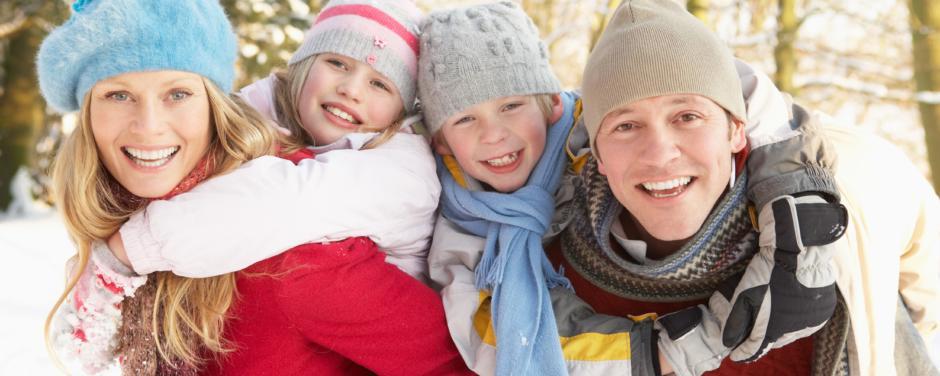 Eltern tragen ihre beiden  Kinder beim einem Winterspaziergang. JUFA Hotels bietet kinderfreundlichen und erlebnisreichen Urlaub für die ganze Familie.