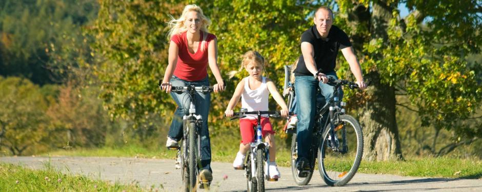 Vater, Mutter und Tochter machen eine Radtour. JUFA Hotels bietet Ihnen den Ort für erlebnisreichen Natururlaub für die ganze Familie.