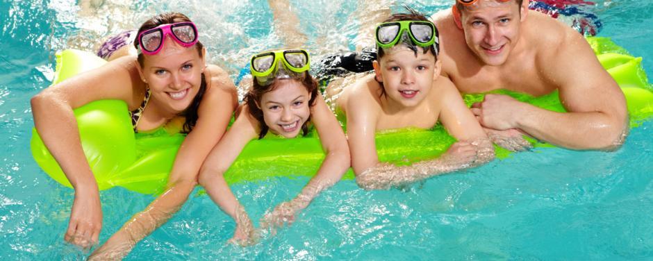 Sie sehen eine Familie mit Schwimmbrillen liegend auf einer grünen Luftmatratze im Pool. JUFA Hotels bietet erholsamen Thermen- und Badespass für die ganze Familie.