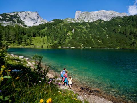 Eine Familie macht eine Wanderpause an einem Bergsee auf der Tauplitz. JUFA Hotels bietet Ihnen den Ort für erlebnisreichen Natururlaub für die ganze Familie.