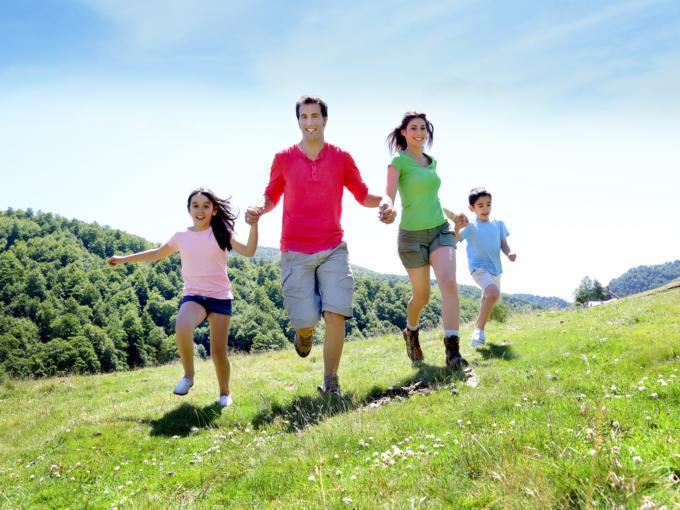 Eine Familie läuft händchenhaltend über eine Wiese. JUFA Hotels bietet kinderfreundlichen und erlebnisreichen Urlaub für die ganze Familie.