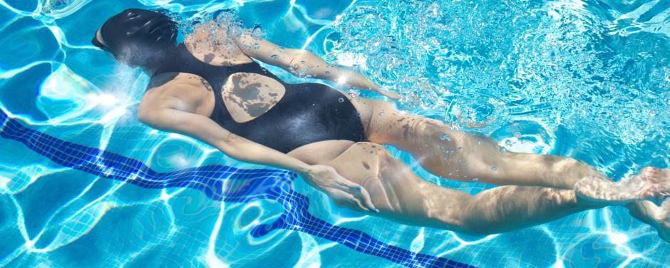 Eine Frau in einem schwarzen Badeanzug taucht in einem Pool im Sommer. JUFA Hotels bietet erholsamen Thermen- und Badespass für die ganze Familie.