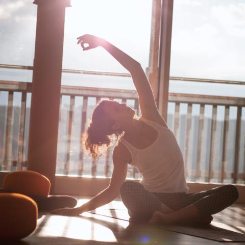 Eine junge Frau sitzt vor einem Fenster im Schneidersitz am Boden und macht eine Yogaübung. JUFA Hotels bietet erholsamen Thermen- und Badespass für die ganze Familie.