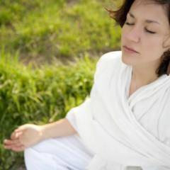 Eine Frau in einem weißen Bademantel sitzt im Schneidersitz in einer grünen Wiese und entspannt sich bei einer Yogaübung. JUFA Hotels bietet erholsamen Thermen- und Badespass für die ganze Familie.