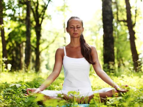 Eine Frau sitzt im Schneidersitz im Wald und entspannt sich bei einer meditativen Yogaübung. JUFA Hotels bietet erholsamen Thermen- und Badespass für die ganze Familie.