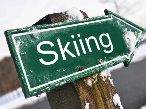 Eine grüne pfeilförmige Tafel mit der Aufschrift Skiing im Winter. JUFA Hotels bietet erholsamen Familienurlaub und einen unvergesslichen Winterurlaub.