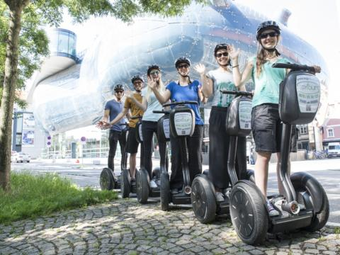 Eine Gruppe von Erwachsenen cruist auf Segways durch die Stadt Graz mit dem Veranstalter SEGYtours. JUFA Hotels bietet erlebnisreichen Städtetrip für die ganze Familie und den idealen Platz für Ihr Seminar.