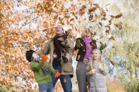 Eine Familie mit zwei Kindern macht einen Herbstspaziergang und freut sich über das bunte Laub. JUFA Hotels bietet Ihnen den Ort für erlebnisreichen Natururlaub für die ganze Familie.