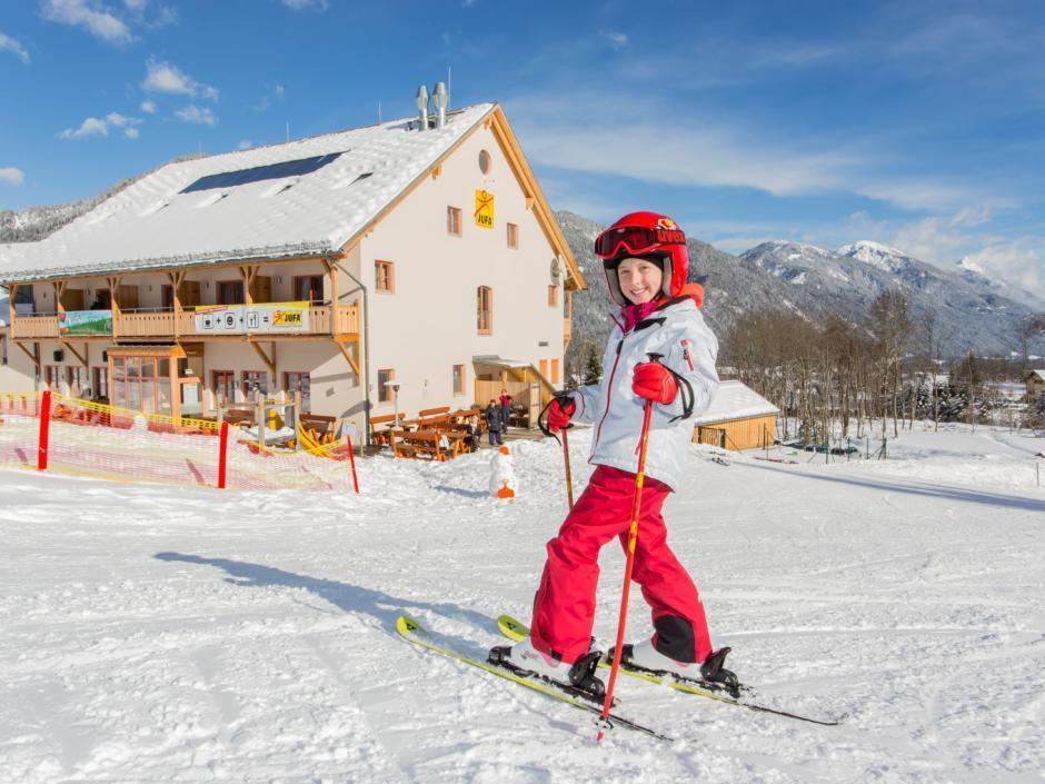 Kind beim Skifahren vorm JUFA Hotel Gitschtal Landerlebnis. Der Ort für erholsamen Familienurlaub und einen unvergesslichen Winterurlaub.
