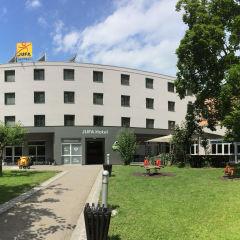 Sommerliche Außenansicht mit Spielplatz vom JUFA Hotel Graz City. Der Ort für erlebnisreichen Städtetrip für die ganze Familie und der ideale Platz für Ihr Seminar.