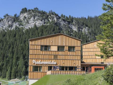 Aussenansicht des JUFA Hotel Malbun Alpin-Resort mit Schriftzug und Bergen im Hintergrund im Sommer. JUFA Hotels bietet erholsamen Familienurlaub und einen unvergesslichen Winterurlaub.