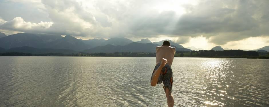 Ein Mann springt von einem Steg in einen See im Allgäuer Seenland in der Nähe vom JUFA Kempten - Familien-Resort. Der Ort für kinderfreundlichen und erlebnisreichen Urlaub für die ganze Familie.