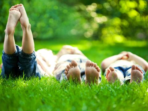 Eine Familie liegt barfuß im Gras. JUFA Hotels bietet kinderfreundlichen und erlebnisreichen Urlaub für die ganze Familie.