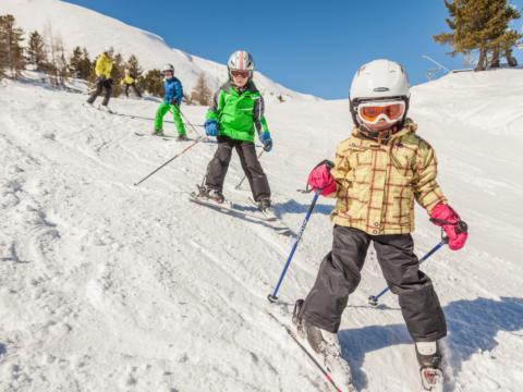 Kinder beim Skifahren im Skigebiet Turracher Höhe in Kärnten. JUFA Hotels bietet erholsamen Familienurlaub und einen unvergesslichen Winterurlaub.