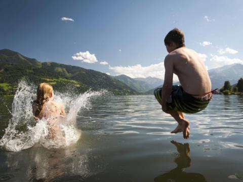 Zwei Kinder springen mit Arschbombe in einen See. JUFA Hotels bietet tollen Sommerurlaub an schönen Seen für die ganze Familie.
