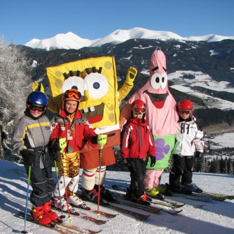 Kindergruppe im Skikurs posiert für ein Foto mit den zwei Maskottchen der Skischule im Skigebiet Gaal in der Steiermark. JUFA Hotels bietet erholsamen Familienurlaub und einen unvergesslichen Winterurlaub.