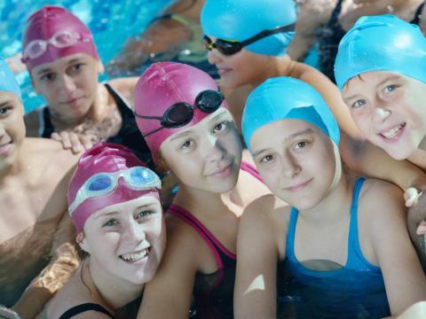 Eine Gruppe von Kindern mit Badehauben stehen im Schwimmbecken und lächeln in die Kamera. JUFA Hotels bietet erholsamen Thermen- und Badespass für die ganze Familie.
