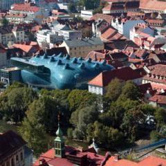Blick vom Schlossberg auf das Kunsthaus Graz im Sommer. JUFA Hotels bietet erlebnisreichen Städtetrip für die ganze Familie und den idealen Platz für Ihr Seminar.