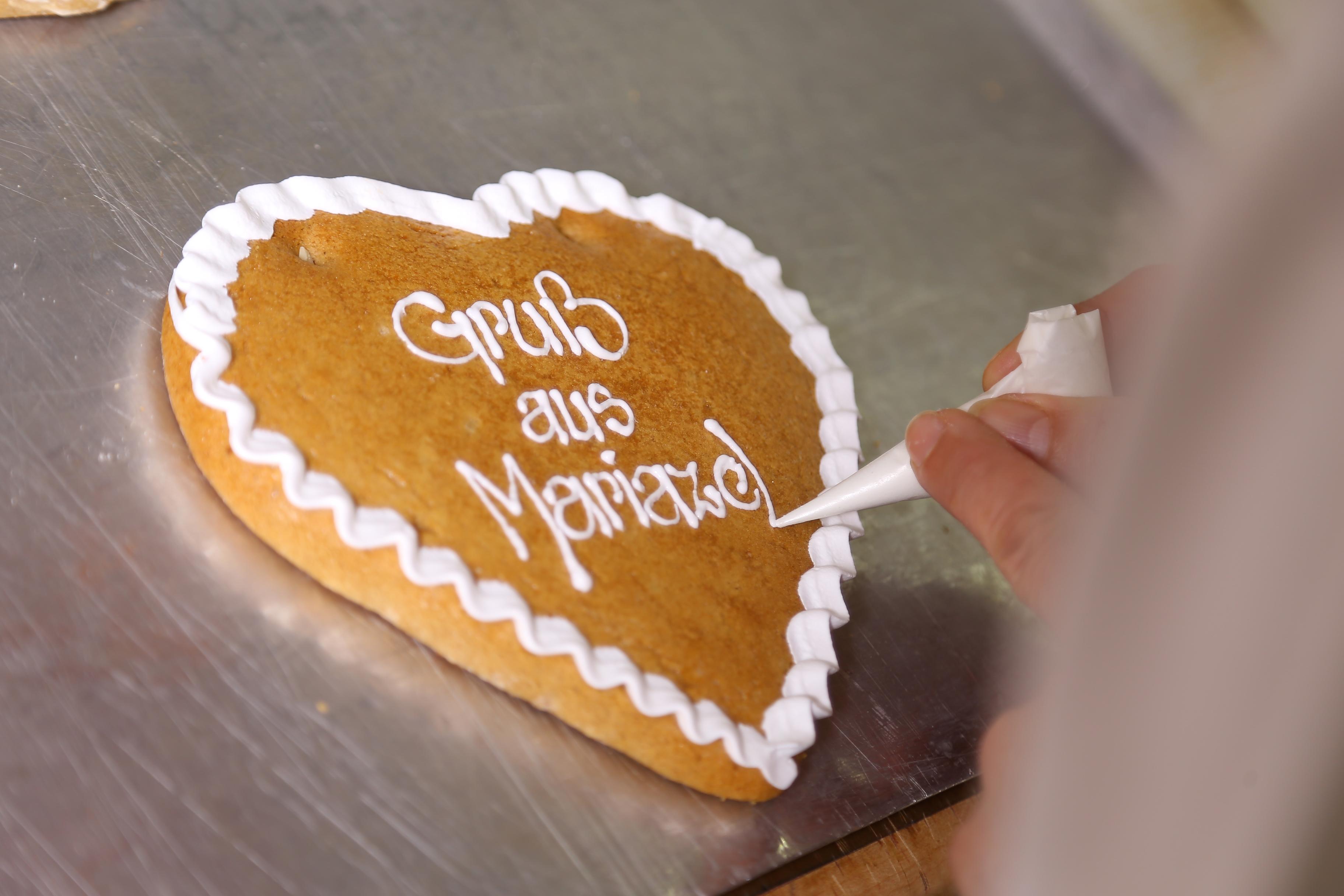 Ein Konditor verziehrt ein Lebkuchenherz mit Zuckerguss in der Lebzelterei Pirker in Mariazell. JUFA Hotels bieten erholsamen Familienurlaub und einen unvergesslichen Winter- und Wanderurlaub.