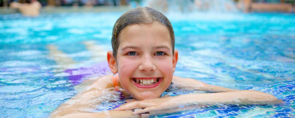 Sie sehen ein Mädchen erholend im Kinderbecken mit einem Wasserfall liegend. JUFA Hotels bietet erholsamen Thermen- und Badespass für die ganze Familie.