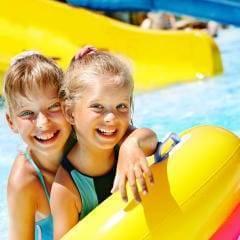 Sie sehen zwei lachende blonde Mädchen mit Schwimmreifen im Freibad mit Rutsche. JUFA Hotels bietet erholsamen Thermen- und Badespass für die ganze Familie.