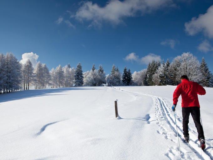 Ein Langläufer folgt einer einzelnen Spur im frischen Schnee. JUFA Hotels bietet erholsamen Familienurlaub und einen unvergesslichen Winterurlaub.