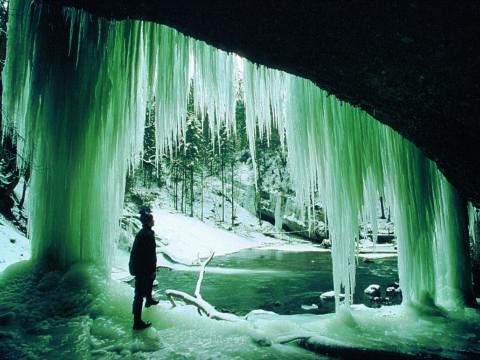 Ein Mann steht unter einem Felsvorsprung mit riesigen Eiszapfen im Naturschutzgebiet Eistobel in Wangen im Allgäu.JUFA Hotels bietet Ihnen den Ort für erlebnisreichen Natururlaub für die ganze Familie.