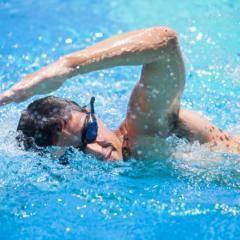 Sie sehen einen Mann mit einer Schwimmbrille beim Kraulen im Pool. JUFA Hotels bietet Ihnen den Ort für erfolgreiches Training in ungezwungener Atmosphäre für Vereine und Teams.