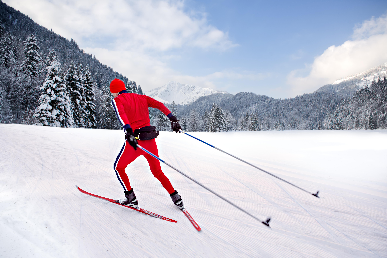 Ein Langläufer skatet auf seinen Langlaufskiern durch eine Winterlandschaft. JUFA Hotels bietet erholsamen Familienurlaub und einen unvergesslichen Winterurlaub.