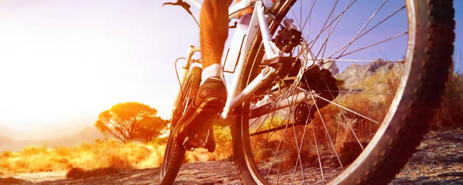 Ein Mann auf einem Mountainbike fährt im Sonnenuntergang über eine Felsplatte. JUFA Hotels bietet Ihnen den Ort für erlebnisreichen Natururlaub für die ganze Familie.