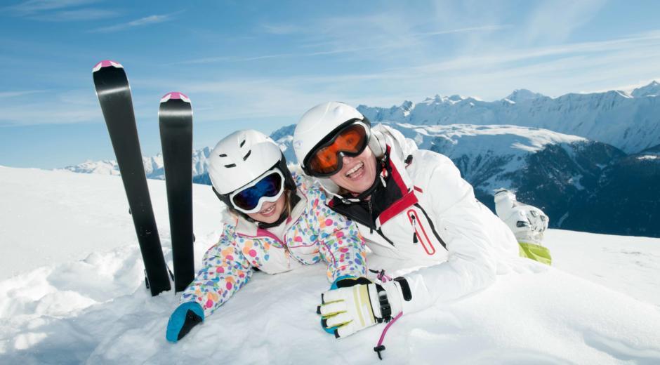 Mutter und Kind liegen beim Skifahren im Schnee und haben Spaß in den Alpen. JUFA Hotels bietet erholsamen Familienurlaub und einen unvergesslichen Winterurlaub.