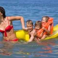 Sie sehen eine Mutter, die drei Kinder auf einer gelben Luftmatratze durch den See zieht. JUFA Hotels bietet kinderfreundlichen und erlebnisreichen Urlaub für die ganze Familie.