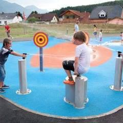 Kinder bei einer lustigen Wasserschlacht im Outdoorspielbereich vom JUFA Hotel Bleiburg - Sport-Resort. Der Ort für erholsamen Familienurlaub und einen unvergesslichen Winter- und Wanderurlaub.