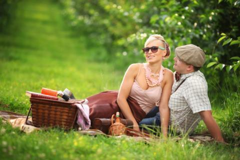 Ein Mann und eine Frau sitzen auf einer grünen Wiese und machen ein Picknick. JUFA Hotels bieten erholsamen Familienurlaub und einen unvergesslichen Wellness- und Wanderurlaub.