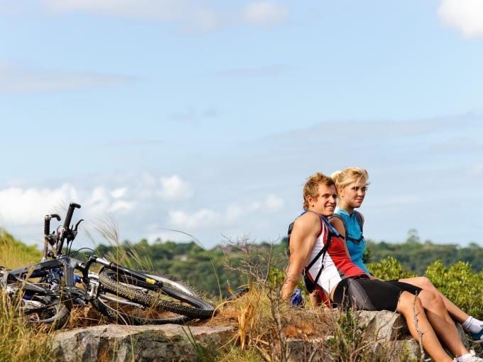 Ein Paar macht eine Pause während einer Mountainbiketour und sitzt auf einem Stein. JUFA Hotels bietet Ihnen den Ort für erlebnisreichen Natururlaub für die ganze Familie.