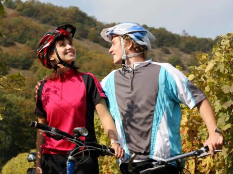 Ein Paar auf Mountainbikes macht Pause zwischen den Weinreben und umarmt sich. JUFA Hotels bietet Ihnen den Ort für erlebnisreichen Natururlaub für die ganze Familie.
