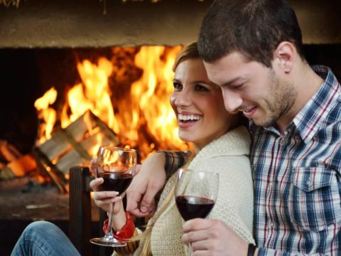 Ein junges Paar sitz vor einem offenen Kamin und trinkt Wein. JUFA Hotels bieten erholsamen Familienurlaub und einen unvergesslichen Wellness- und Wanderurlaub.