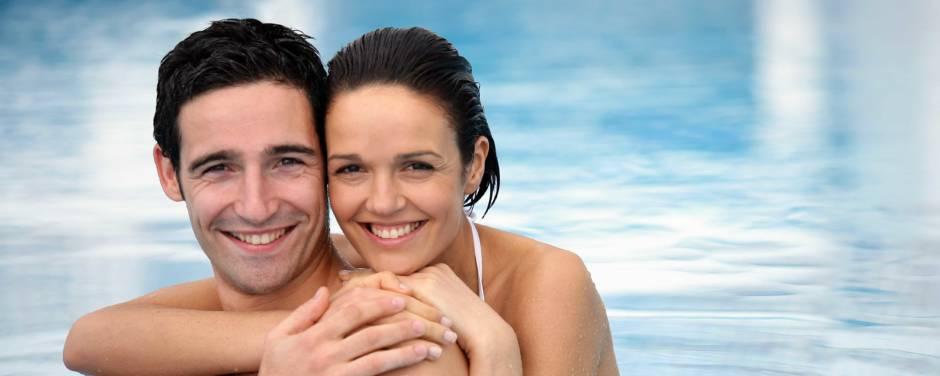 Sie sehen ein Paar im Pool stehend und sich die Frau den Mann von hinten umarmt. JUFA Hotels bietet erholsamen Thermen- und Badespass für die ganze Familie.