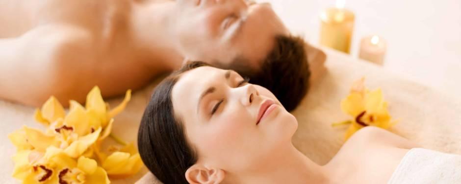 Ein Paar beim Wellnessen liegt Kopf an Kopf auf einer Liege und entspannt sich. JUFA Hotels bietet erholsamen Thermen- und Badespass für die ganze Familie.