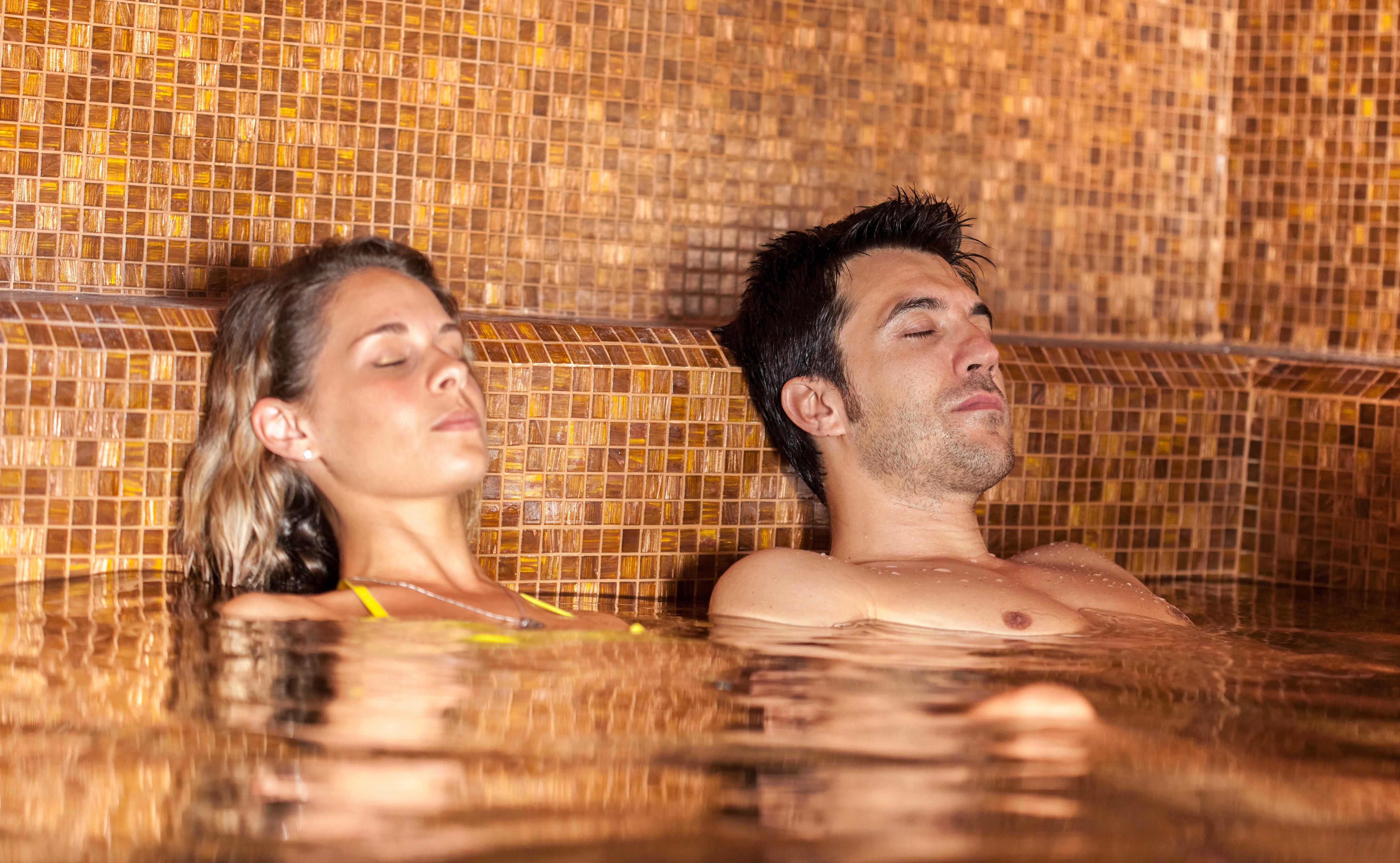 Sie sehen ein Paar liegend und erholend im Thermalbecken. JUFA Hotels bietet erholsamen Thermen- und Badespass für die ganze Familie.