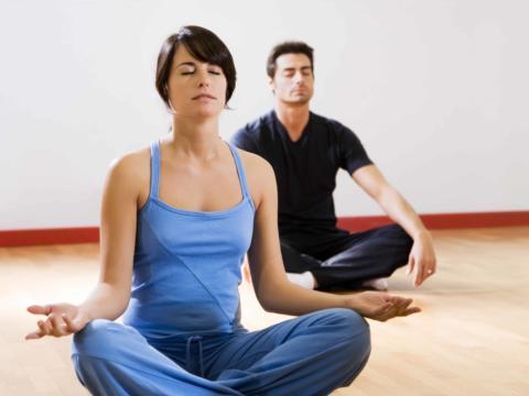 Eine Frau und ein Mann sitzen im Scheidersitz auf dem Boden und machen Yoga. JUFA Hotels bietet erholsamen Thermen- und Badespass für die ganze Familie.