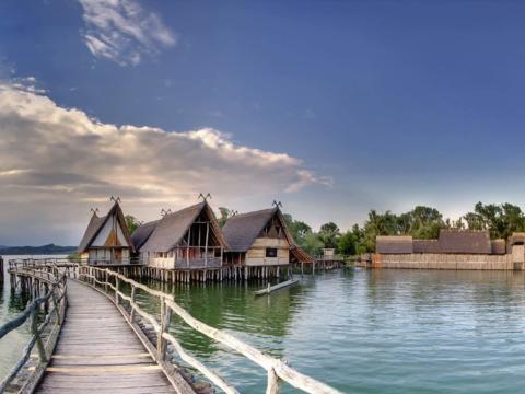 Aussenansicht der Pfahlbauten von Unteruhldingen mit Steg im Vordergrund in der Nähe vom JUFA Hotel Meersburg. Der Ort für tollen Sommerurlaub an schönen Seen für die ganze Familie.