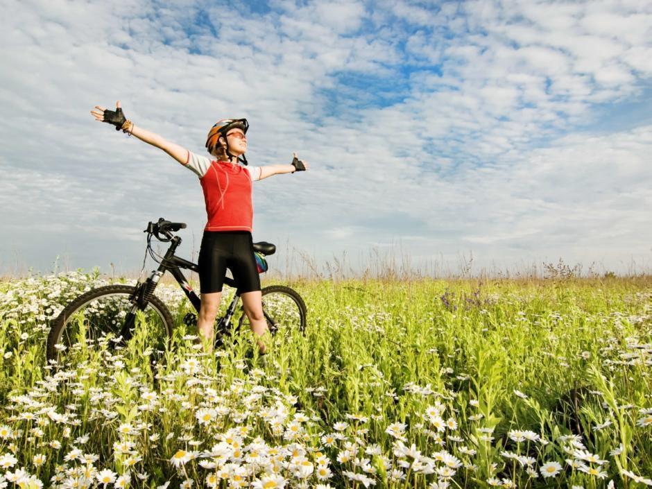 Ein Mann mit einem Mountainbike steht mitten in einer Blumenwiese und genießt während einer Pause die Natur. JUFA Hotels bietet Ihnen den Ort für erlebnisreichen Natururlaub für die ganze Familie.