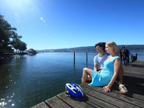 Sie sehen zwei Radler am Steg sitzend in Reichenau am Bodensee. JUFA Hotels bieten erholsamen Familienurlaub und einen unvergesslichen Winter- und Wanderurlaub