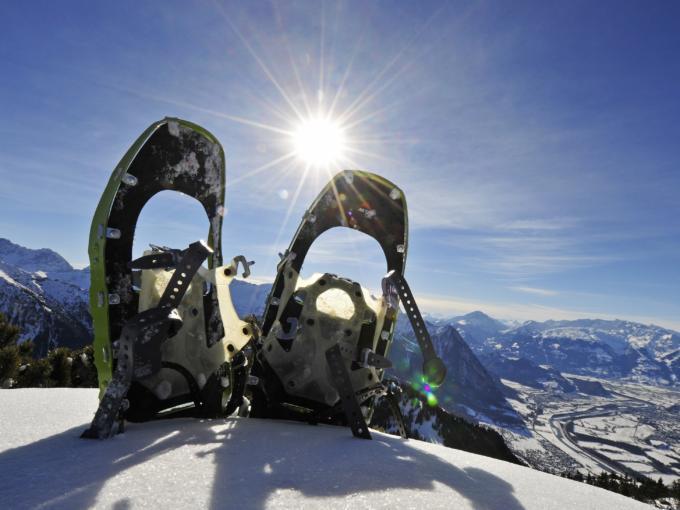 Ein paar Schneeschuhe steckt vor einem winterlichen Bergpanorama im Schnee. JUFA Hotels bietet erholsamen Familienurlaub und einen unvergesslichen Winterurlaub.