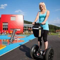 Frau beim Segway-Fahren vor dem JUFA Hotel Bleiburg - Sport-Resort. JUFA Hotels bietet Ihnen den Ort für erfolgreiches Training in ungezwungener Atmosphäre für Vereine und Teams.