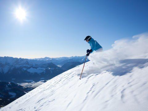 Skifahrer beim Skifahren abseits der Piste in den Alpen. JUFA Hotels bietet erholsamen Familienurlaub und einen unvergesslichen Winterurlaub.